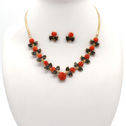Necklace and earrings with bright red Akka coral flower blooms and dark green jade leaf stones along a gold plated chain
