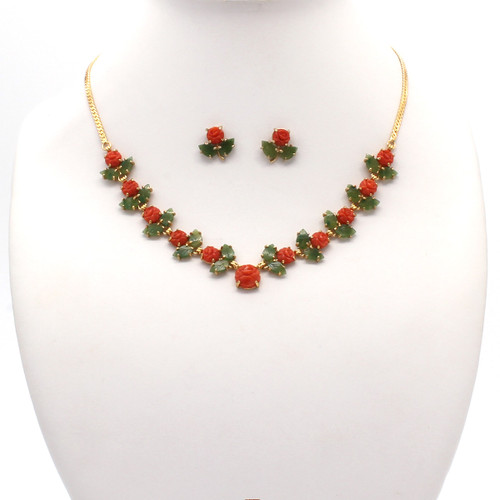 Necklace and earring set with rich red, round coral flowers accompanied by light green jade leaf stones alone a gold plated chain