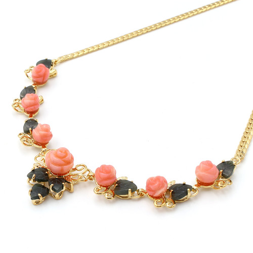 Bright light pink coral roses with dark green jade leaves in a real gold setting, necklace