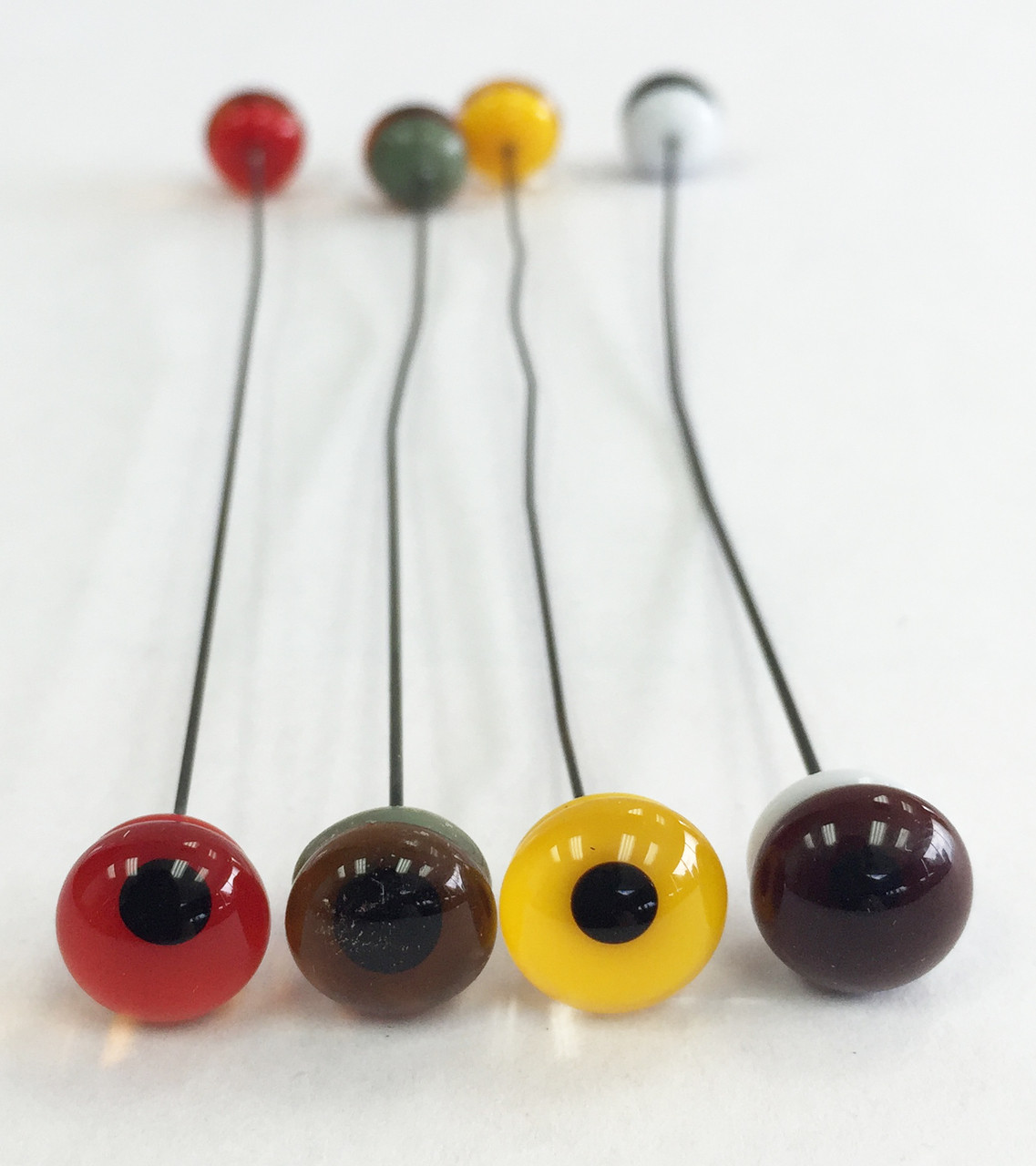 Museum Quality Glass Eyes.  Shown are one of each color glass eye from left:  Red, Hazel, Yellow and Brown.