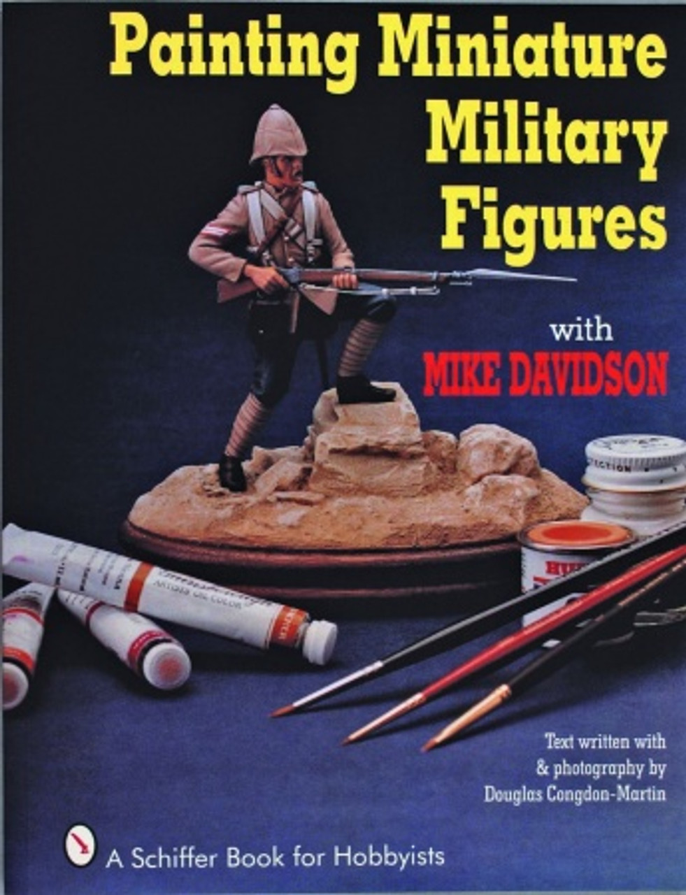 Painting Miniature Military Figures showing a soldier standing on a rock with his gun propped on his knee.