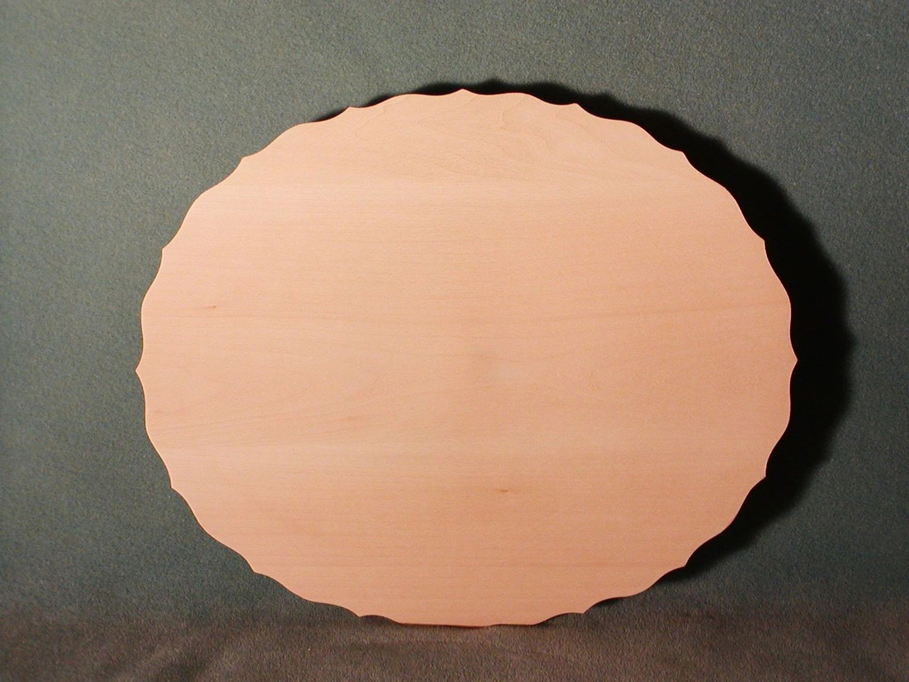 Basswood scalloped oval plate showing the face with the scalloped edges and flat face.