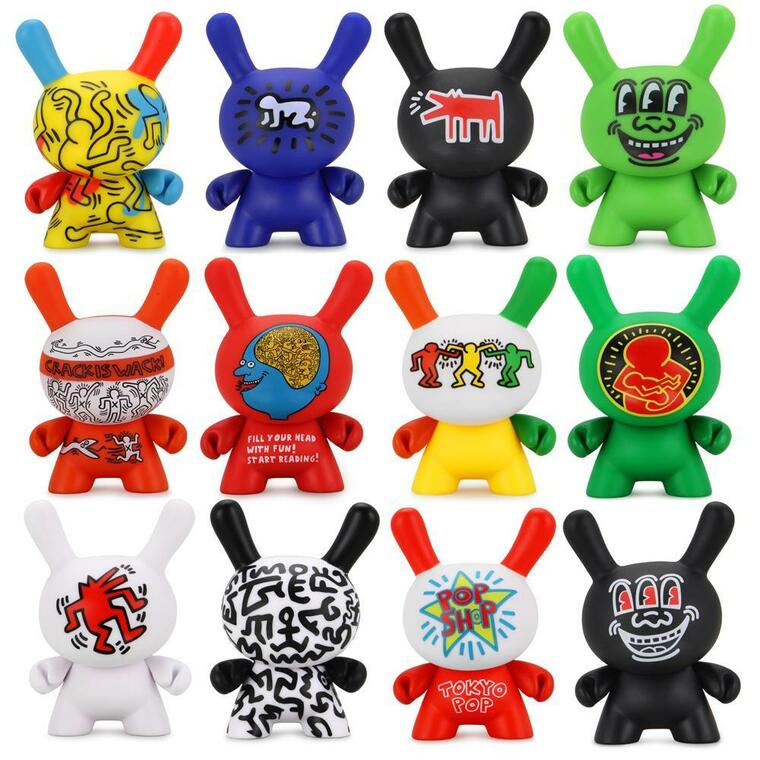 Image of 12 unique and colorful dunny figurines printed with artwork from Keith Haring. These collectible toys have ears like rabbits, round heads and bodies, and arms that can be swiveled.