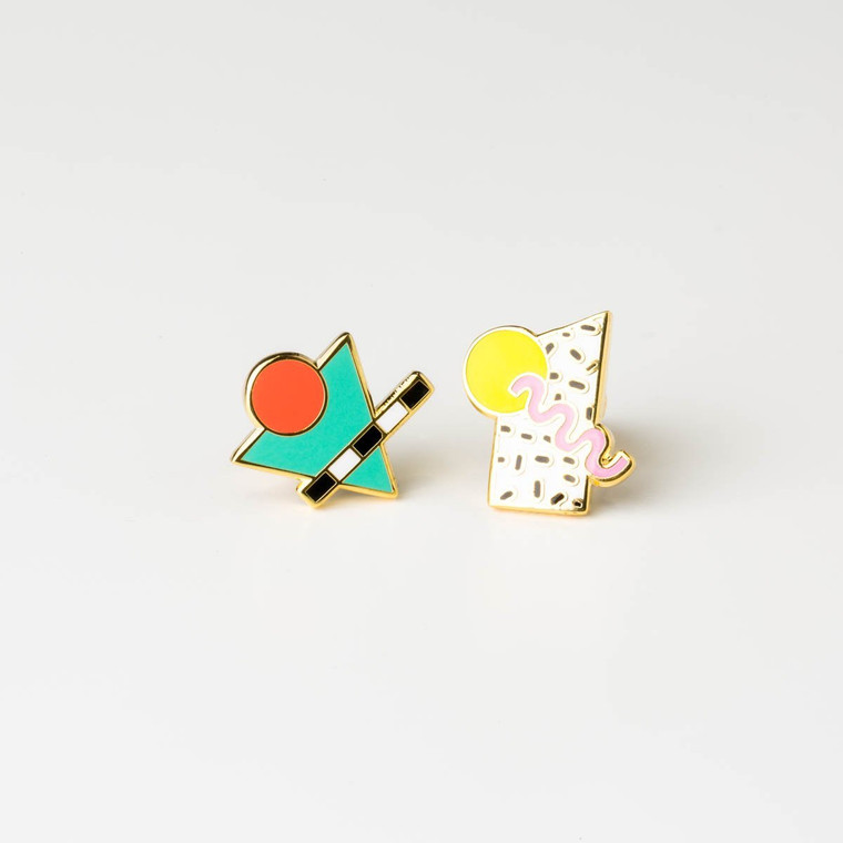 Image of a pair of mismatched gold-plated and enameled earrings with funky 80's Memphis style shapes and colors. Hot orange circle, teal triangle and a black and white patterned stripe on one,  a yellow circle, black and white spotted rhombus and a light pink squiggle on the other.