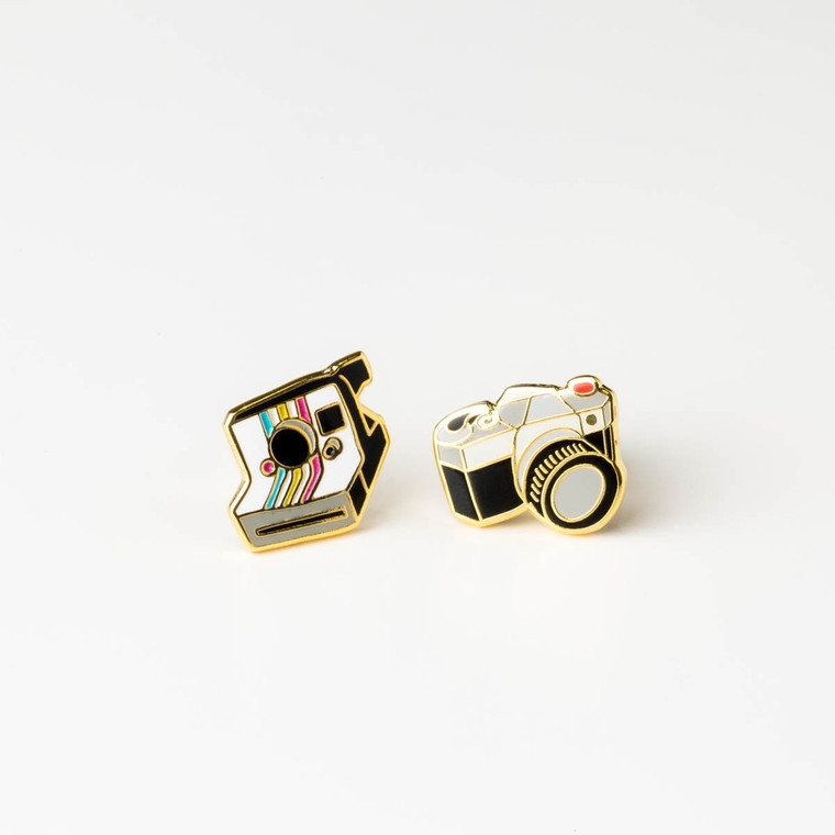 Image of a pair of mismatched gold-plated and enameled post earrings. One is a traditional film camera, the other, an instant camera.