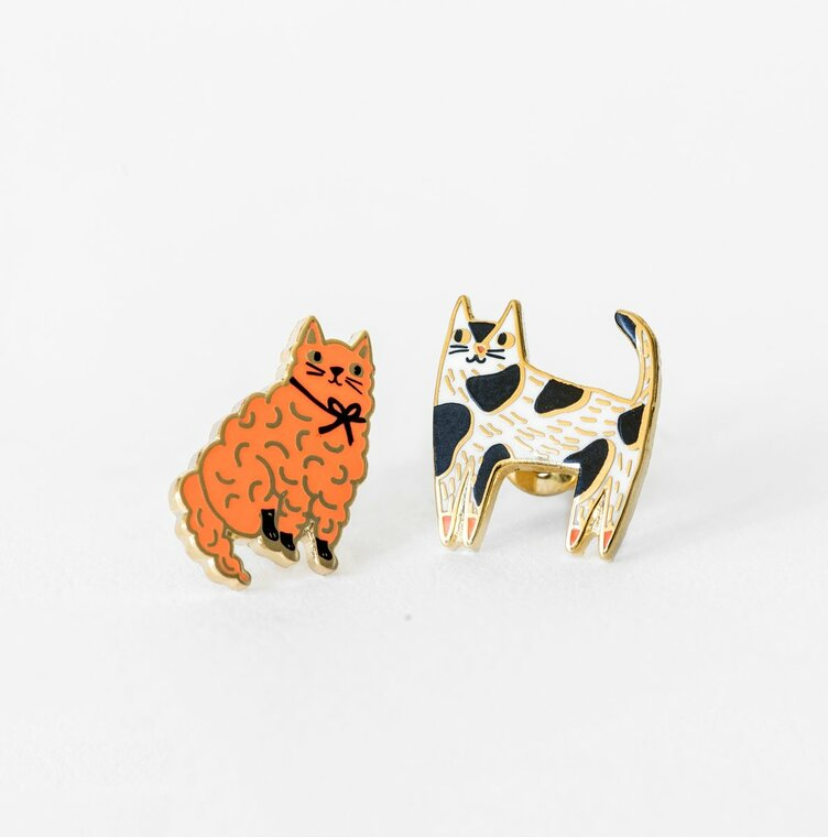 Image of a pair of mismatched gold-plated and enameled post cat earrings, one is pink, the other has black and white spots.