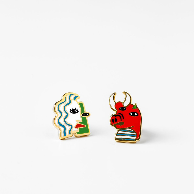 Image of a pair of mismatched gold-plated and enameled post Cubist style graphic earrings. One earring depicts a face, the other depicts a boar-like creature, each with features askew.