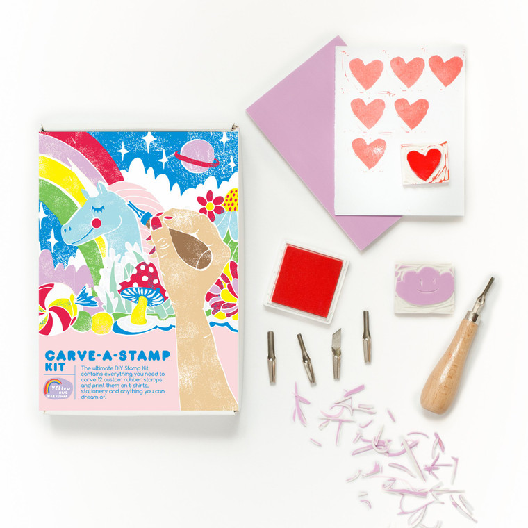 Image of a stamping kit box with a unicorn on it and beside the box is a square stamper carved into a cloud, an ink pad, carving tools, carved off rubber stamp scraps, and a stamped sheet of paper and pink envelope.