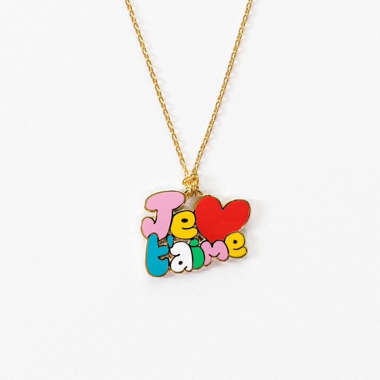 Image of a necklace on a gold chain with a pendant that reads je t'aime in colorful bubble letters.