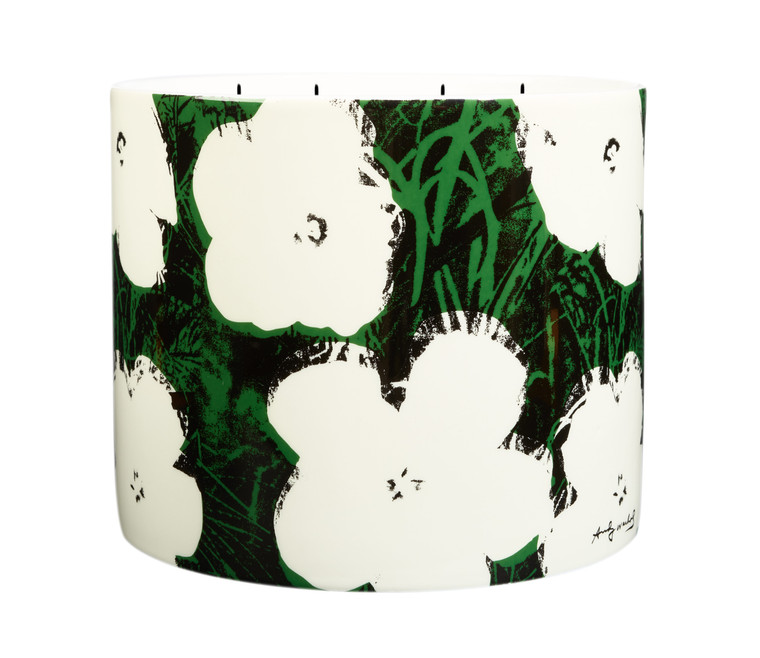 """Image of a large porcelain cylinder with a candle inside printed with Andy Warhols """"Flowers"""" in green and black with white flowers."""
