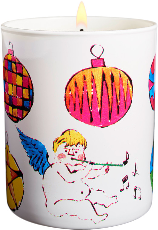 """Image of a lit round candle that is printed with a large cherub and ornaments printed in yellow, pink and blue, a design from Andy Warhols' """"HOLIDAY 2016 / ANGEL""""."""