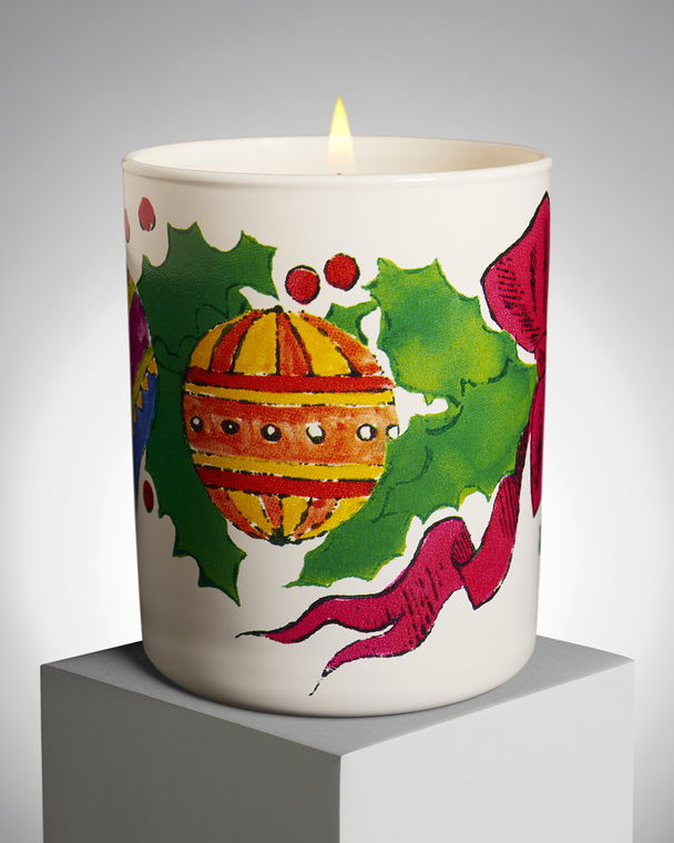 A porcelain candle holder with a drawing of Christmas ornaments and greens