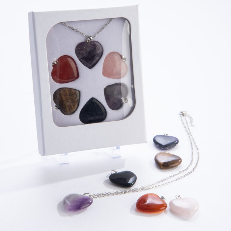 This image show a gemstone heart pendant on a chain in a box with 5 different interchangeable heart pendants.