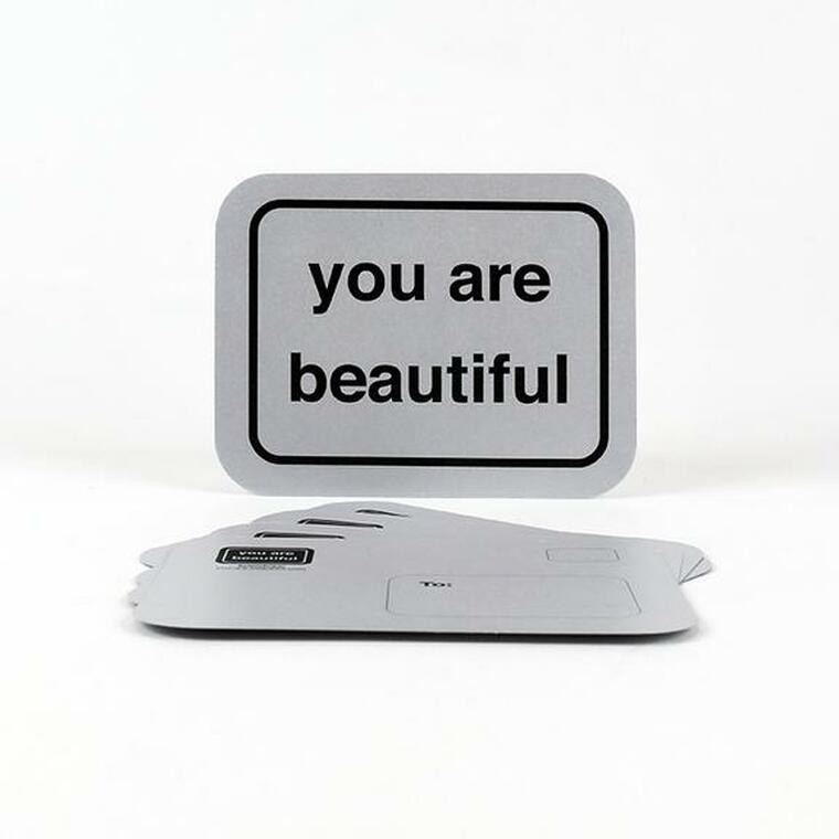 """silver post card imprinted in black bold font """"you are beautiful"""" with black borderline, rounded corners"""