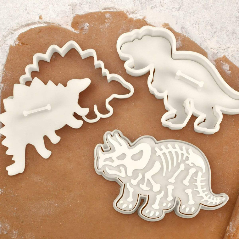 Three dinosaur shaped cookie cutters, with skeleton stamp.
