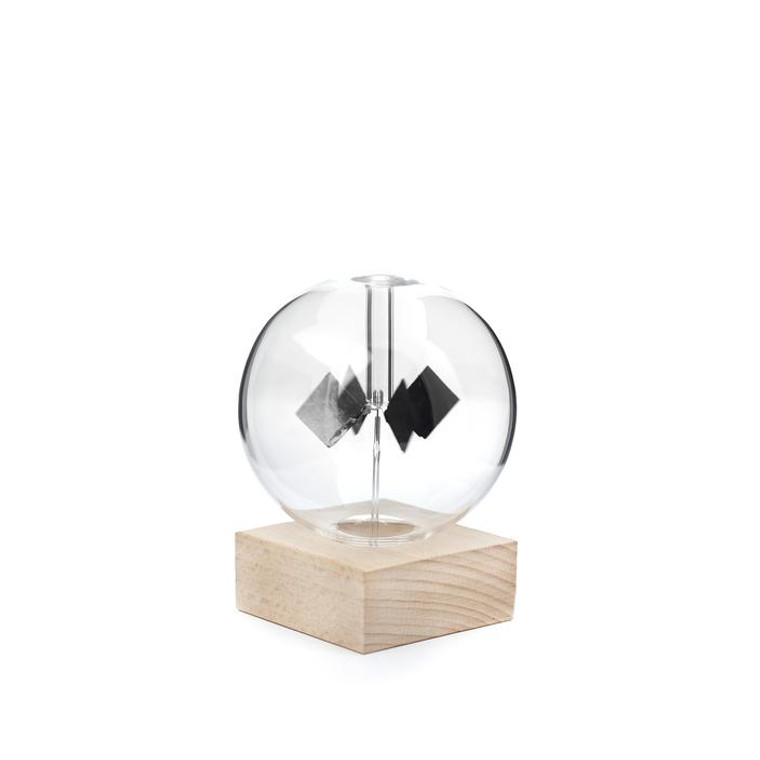 This image shows a clear glass globe with 4 diamond shaped wings in the center that spin in the sunlight. Sits on a wood base.