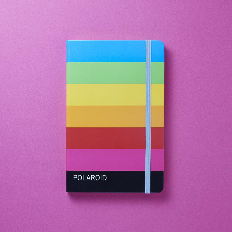 Photo of a notebook on a pink background with colorful horizontal stripes inspired by Polaroid film packaging, and a blue elastic band holding the notebook shut.