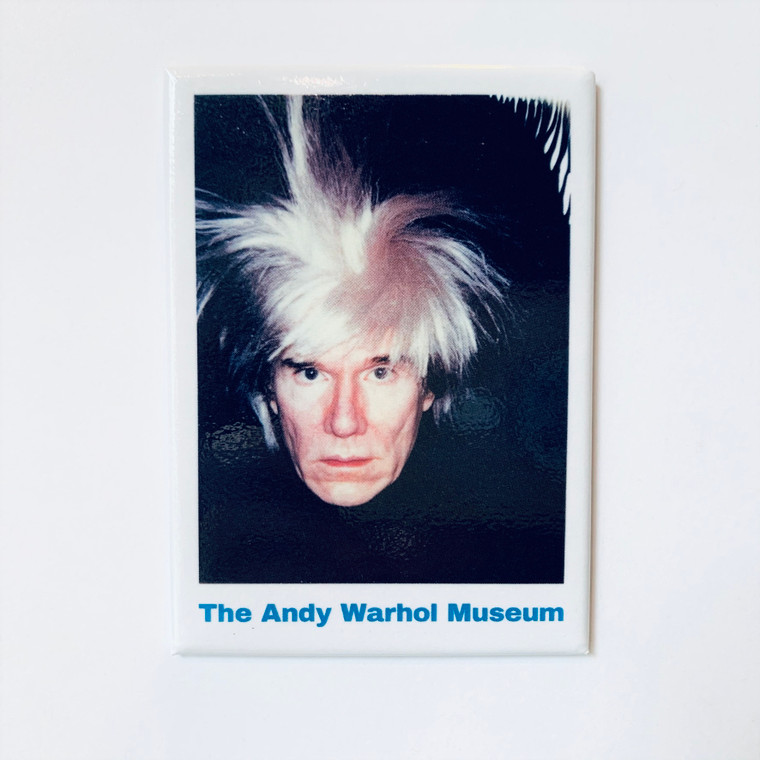 Image of a white rectangular magnet with a dark portrait of Andy Warhol, looking stoic but wearing a wig with white hair standing on end. The bottom of the magnet reads The Andy Warhol Museum in blue text.