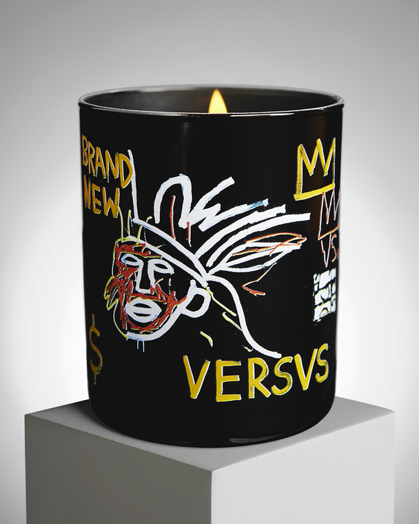 Image of a lit candle with Jean Michel Basquiat's untitled work with a black background, featuring a person wearing a headdress, a dollar sign and the word VERSUS.