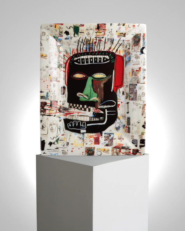 Image of a tray on a pedestal with the work of Basquiat printed on it. The artwork features a maddened face of a person on a white tray.