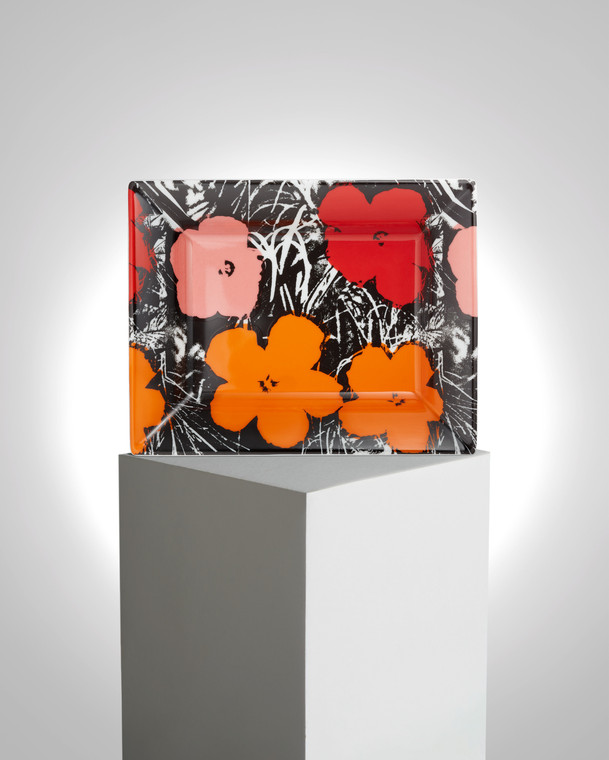Image of a tray on a pedestal with the work of Andy Warhol printed on it. The work features flowers printed in red, pink and orange with black grasses around it on a white try.