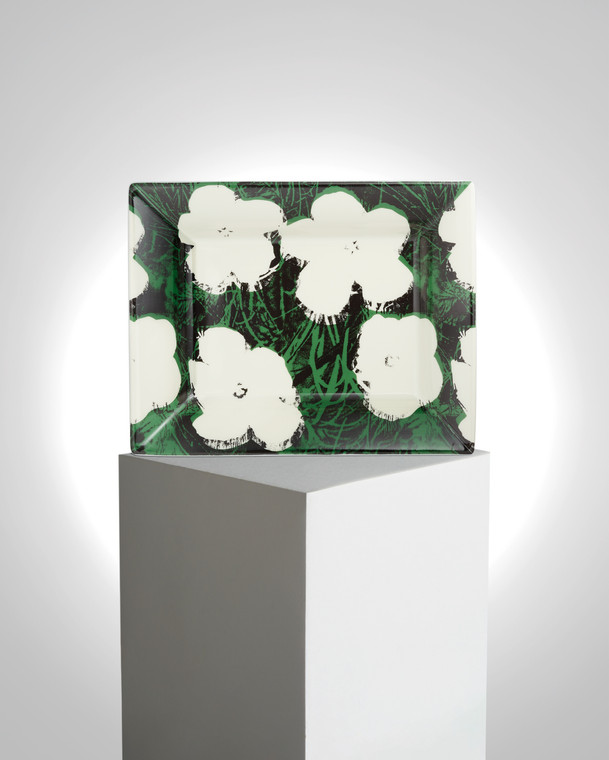 Image of a tray on a pedestal with the work of Andy Warhol printed on it. The work features white flowers with black grasses around it on a white try.
