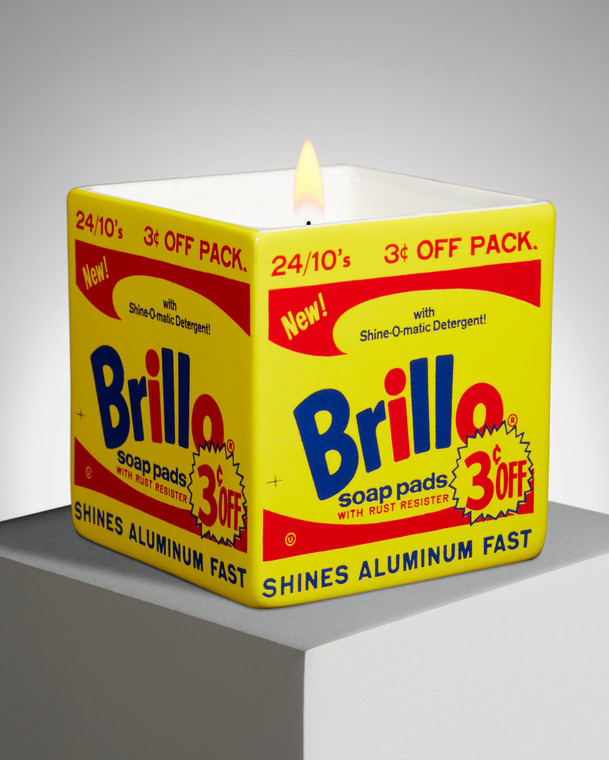 Image of a lit square candle with Andy Warhol's Brillo box in yellow.