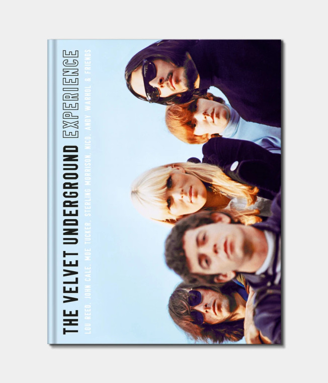 Image of the cover of a book with a sky blue cover that features a sideways picture of the band The Velvet Underground, and the text The Velvet Underground experience printed in black, also sideways.