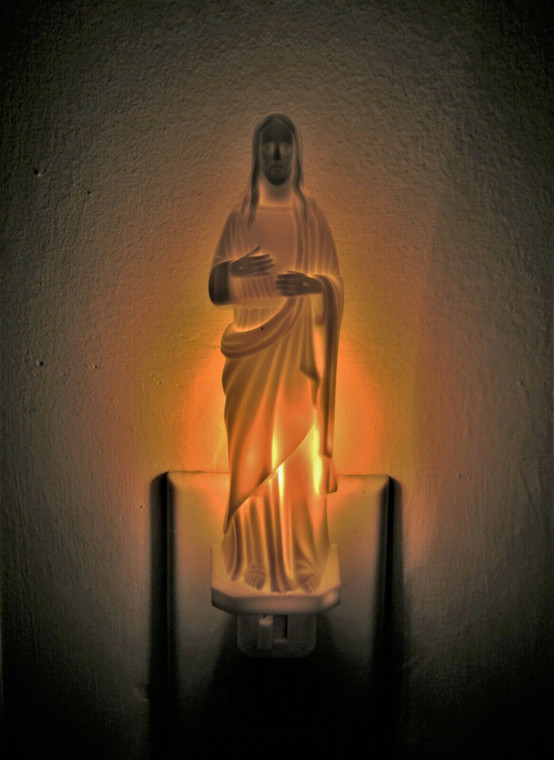 Image of a glowing plastic nightlight shaped like Jesus Christ plugged into a wall.