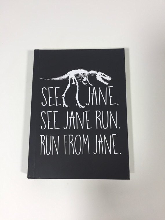 "Black hardback journal with T-Rex fossil sandwiched between the text ""See Jane, See Jane Run, Run From Jane, imprinted in white."