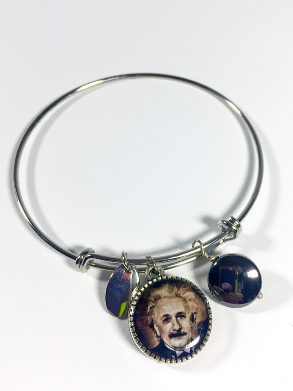 """This image shows a slim silver band with a silver, hematite, and circular charm with an Einstein image on one side and his quote """"Any fool can know, the point is to understand"""" on the other side."""