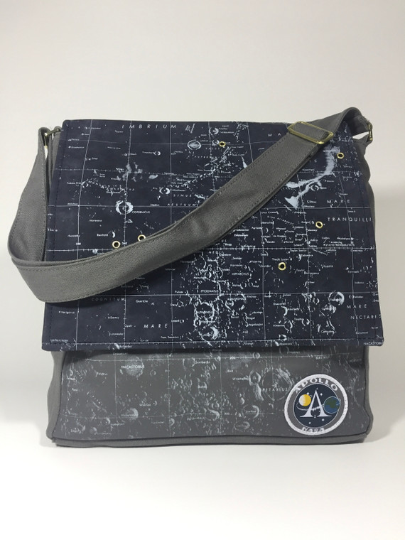 This image shows a gray messenger style bag with a map showing moon on the fabric.  There are metal grommets detailing locations of actual landings.  There are several pockets inside, one is padded for laptop transport.