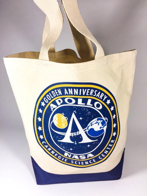 This image show a natural colored canvas bag with the Apollo 50th anniversary image on both sides. It has a fabric handle and a navy blue fabric on the bottom.