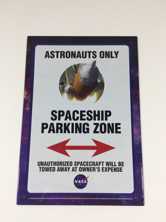 This image shows a rectangular metal sign.  There is a white background with a galaxy border.  The top of the sign has the words astronauts only, below that is a picture of a spaceship, and the words spaceship parking zone, below that is a red arrow pointing left and right, and the bottom states that unauthorized spacecraft will b e towed at owner's expense and the NASA logo.