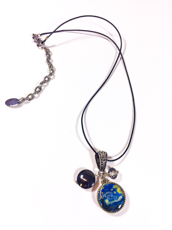 This image show a 3 charm necklace on a black leather band with a silver color clasp.  The 3 charms are a crystal, hematite, and a circular charm with Vincent Van Gogh Starry Night image on both sides.