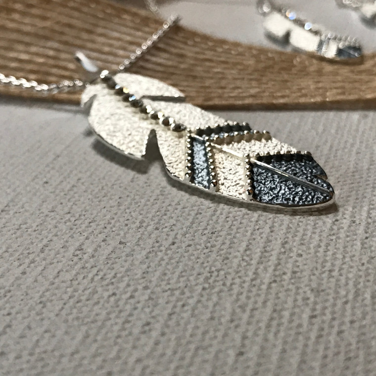 """This beautiful eagle feather features a mix of silver and gray tones, accented with a row of clear cubic zirconias. The sparkly and delicate chain adjusts from 16"""" to 20"""" in length 100% hypoallergenic: Completely lead-free, nickel-free and cadmium free"""