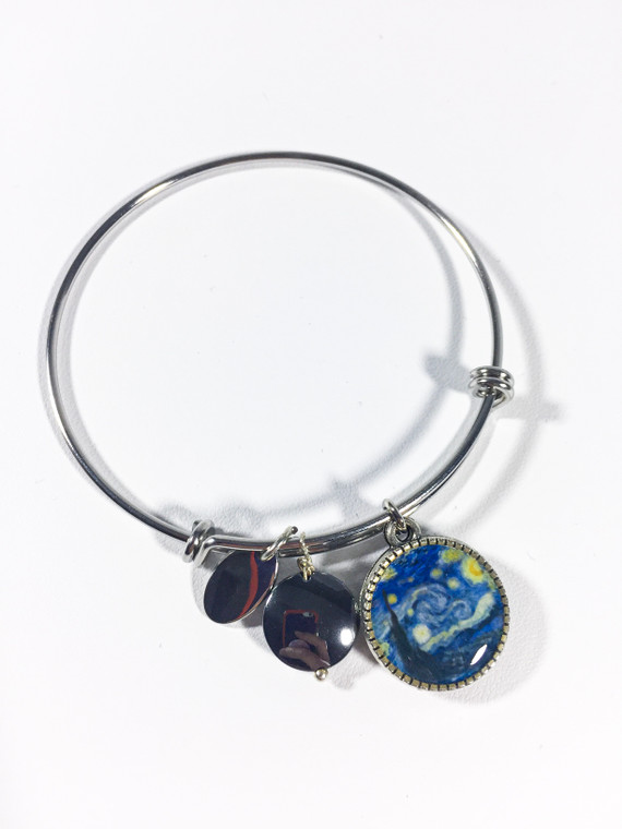 This image show a slim silver bracelet band with 3  charms.  One is a small silver charm, one hematite and the other circular charm with Vincent Van Gogh Starry Night image on both sides.