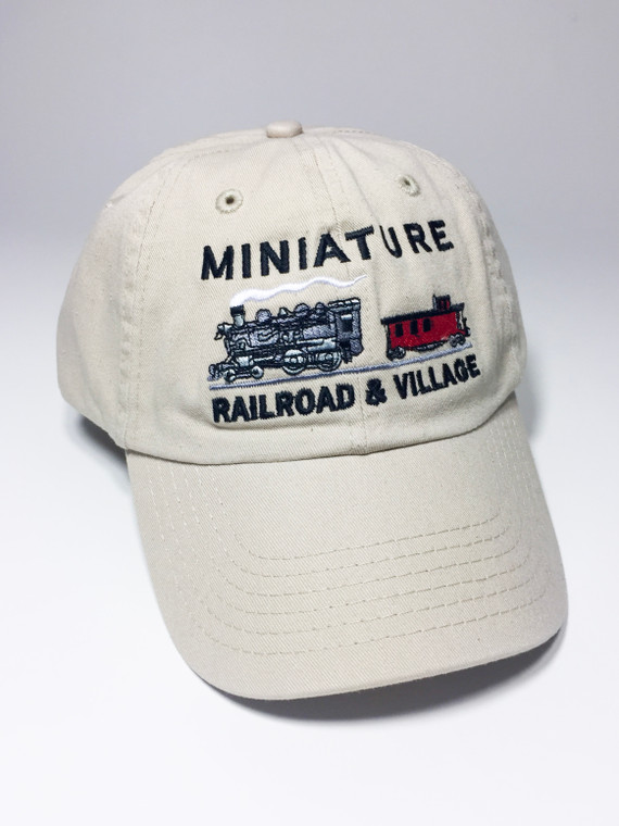 This image is a light beige cap with an embroidered train and caboose along with the words Miniature Railroad and Village on the front.  The back has a metal adjustable band.