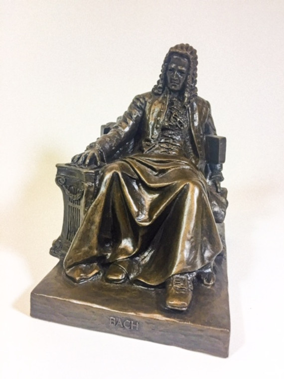 Bronze statue of Bach sitting with his hand on a small pipe organ.