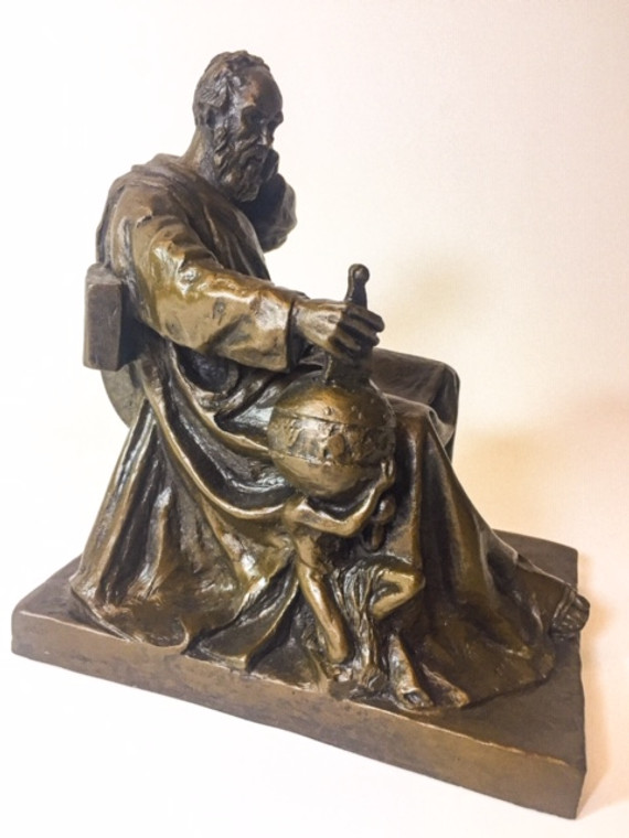 The Galileo statue is sitting next to an atlas holding a sphere.