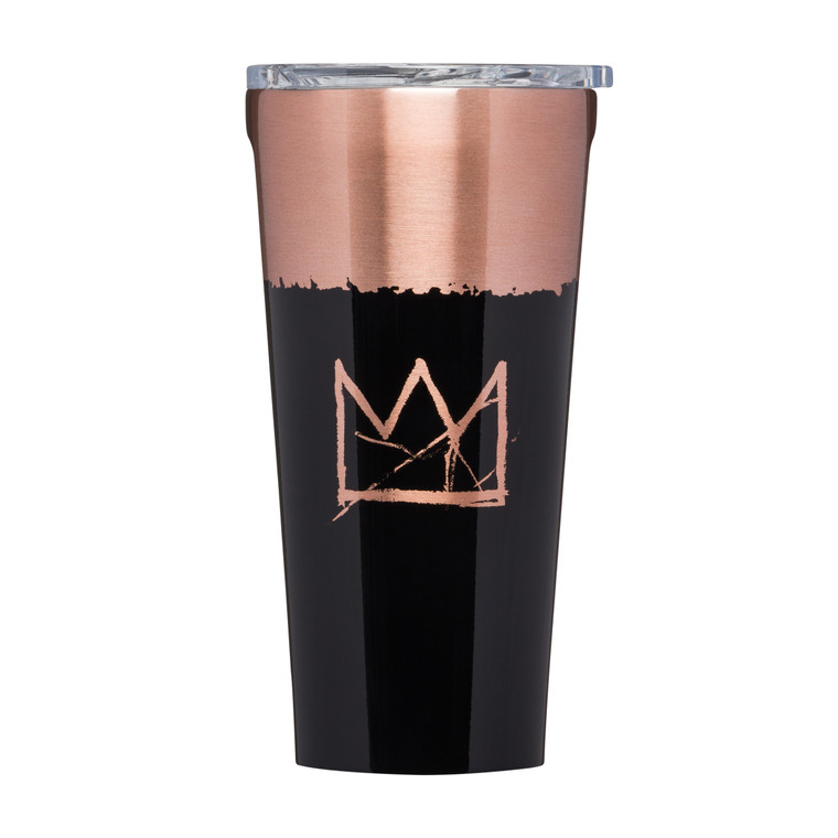 Image of a brass and black coffee tumbler with Basquiat's signature crown printed on it, and a clear lid.