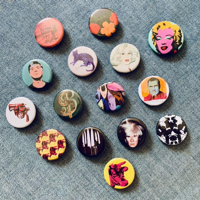 Image of assorted pinback buttons each printed with a different work of Andy Warhol's.