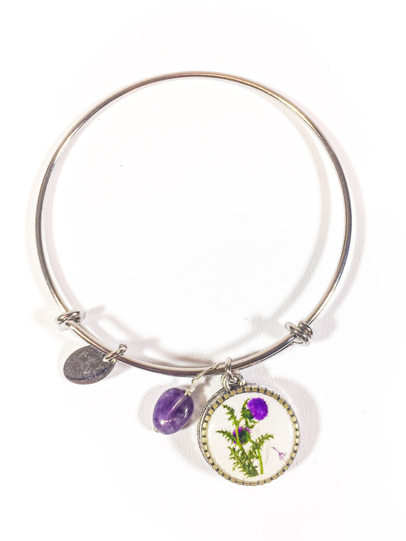 Stainless steel bangle bracelet with a Thistle with alloy metal charm and coordinating gemstone.