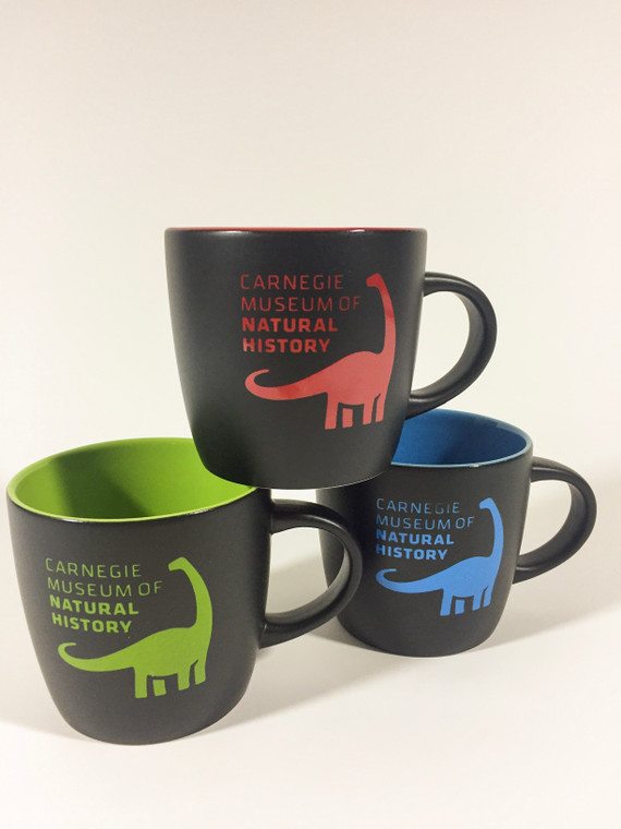 Three stacked mugs in three color variations red, green and blue . Black matte exterior with bright color imprint of dinosaur and museum text logo. Interior of mug is glazed in same color as exterior imprint.