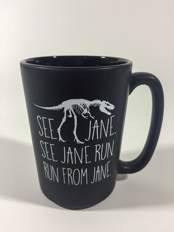 "Black matte 12 oz ceramic mug imprinted in white T-rex fossil sandwiched between the text "" See Jane, See Jane Run, Run from Jane"".  With the Carnegie Museum of Natural History logo on the side."