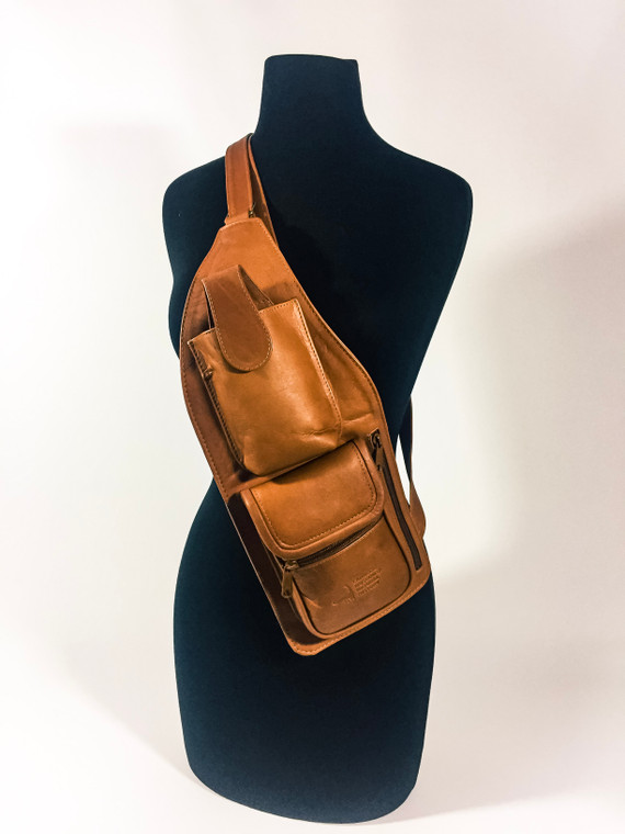 Tan Leather cross body travel bag with an adjustable strap and a side zipper on the side. It has a top pouch for a cell phone and a double bottom compartment with snap and zipper closure, featuring the Carnegie Natural History logo embossed on the bottom compartment in the front. featuring the Carnegie Natural History logo.