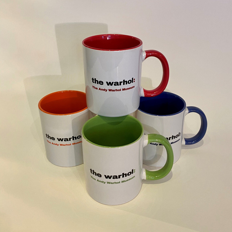 "Four white mugs with colored handles, with the words ""The Warhol: The Andy Warhol Museum"" in matching colors"