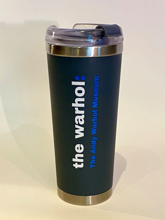 """A dark grey travel tumlber with silvertone metal accents and plastic top, with the words """"The Warhol: in white and """"The Andy Warhol Museum"""" in blue"""
