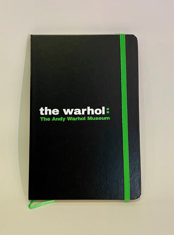 "A black notebook with white ""The Warhol"" and green  ""The Andy Warhol Museum"" and green elestic closure"