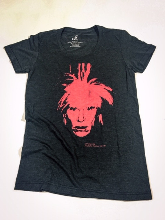 """A dark heathered gray t-shirt with a red Self Portrait of Warhol in a """"fright"""" wig."""